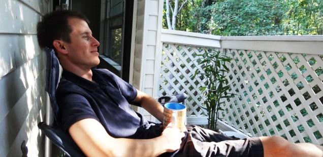 im stuhl auf dem balkon sitzend tee trinken