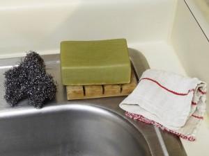 olivenseifenstueck, lappen und stahlwolle am waschbecken