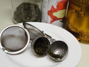 loser tee in metall teesieben auf einem teller mit drei dosen tee im hintergrund