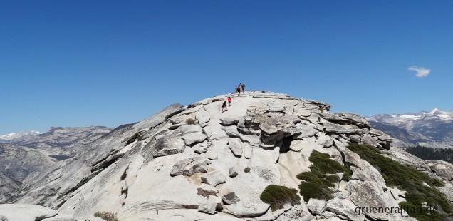 Menschen klettern auf eine hohe Bergspitze