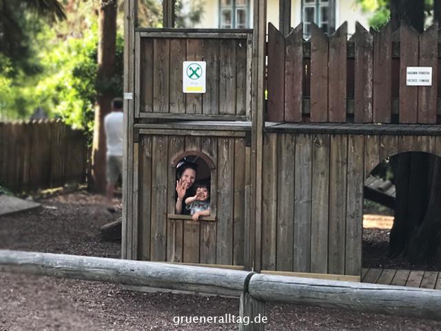 Sohn und Mama schauen aus der Spielplatzburg