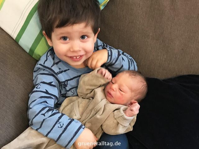 großer Bruder hält neugeborenen Bruder im Arm