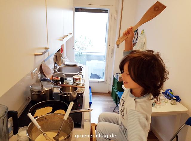 Kind beim Pfannkuchen braten